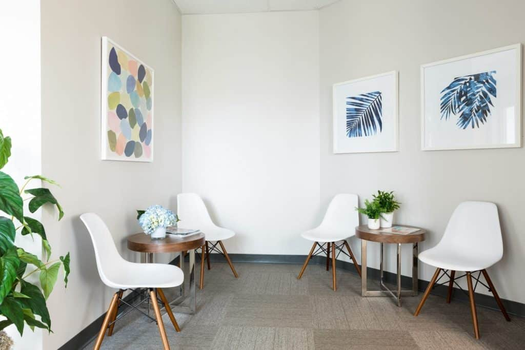 Photo showing several chairs and plants with pictures on the wall of Kimberly Arcara's office space in their North Borough office location.