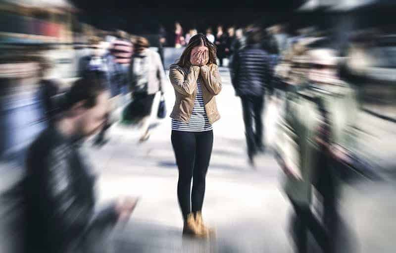 Photo of a girl having a panic attack in the middle of a busy crowd