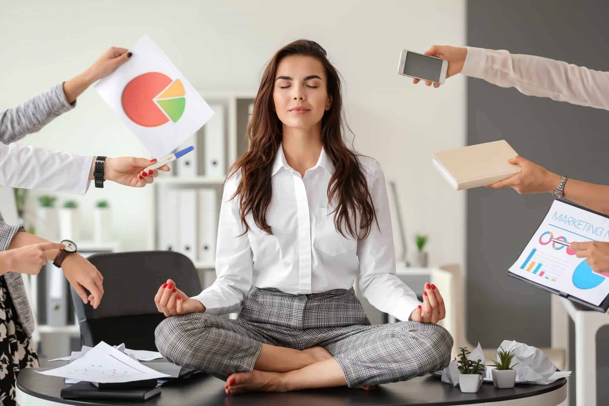Business woman coping with stress around her through meditation