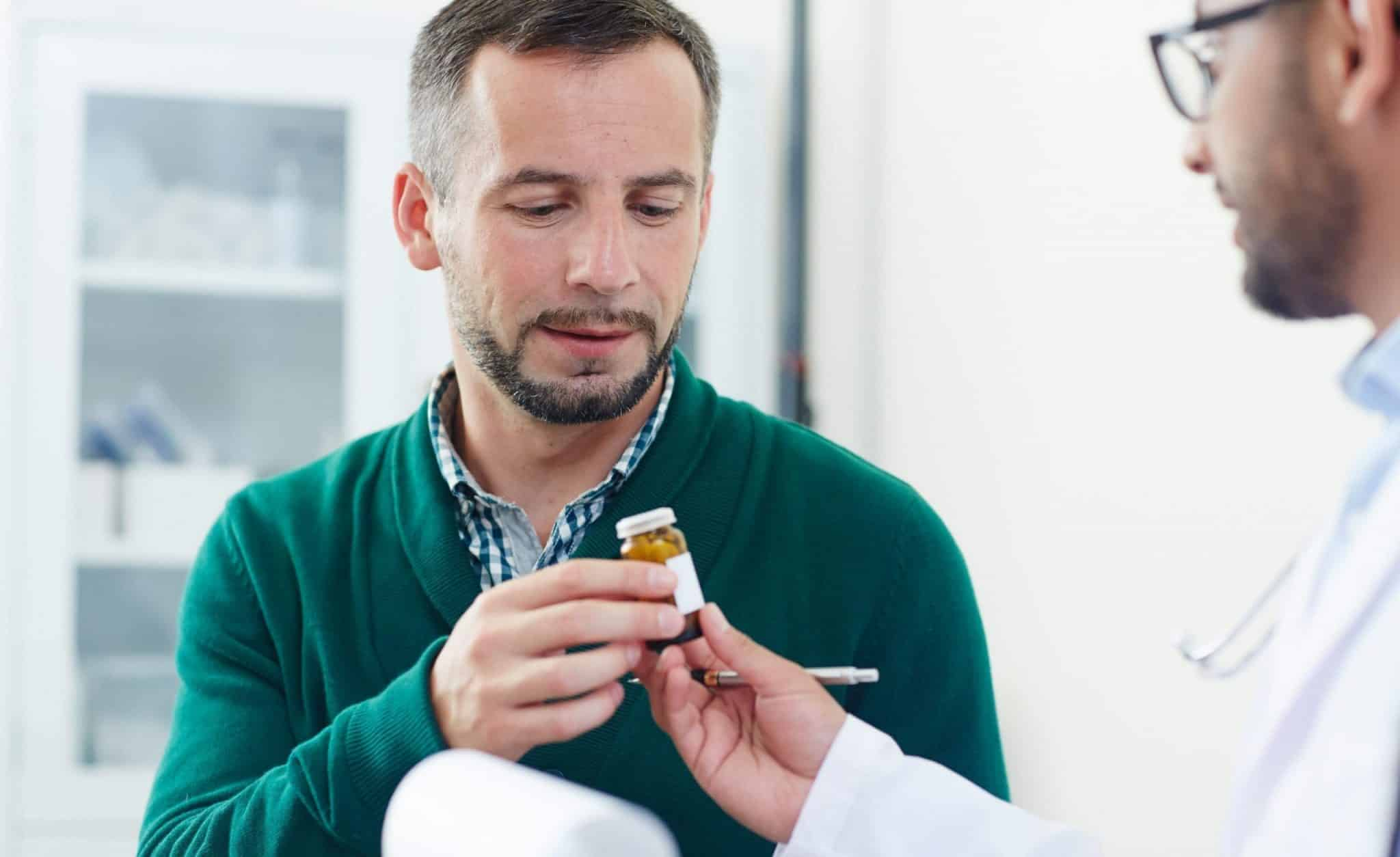 Man consulting with a doctor who is handing him medication